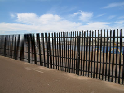 A long row of black powder coated palisade fencing around the sea and there is a ship in the sea.
