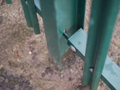 The green powder coated RSJ beam palisade post is fixed in the ground.