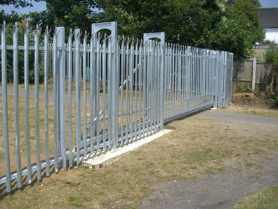A galvanized palisade sliding gate for a place is closed, some sections of the gate are overlapped with the palisade fence.