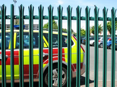 Green triple pointed palisade fence with W pale section serves as the fence for the parking lot.