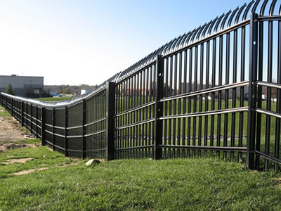 On a vast grassland, a row of high palisade fence follow the uneven terrains, the top of the fence is bending.