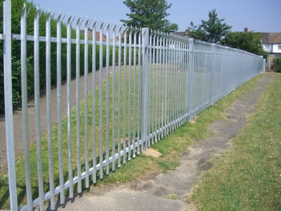 A long row of galvanized palisade fence serves as the security fence to separate the greenbelt and the outside.