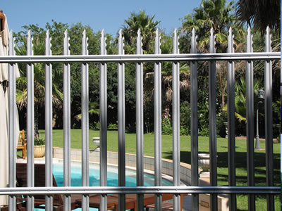 Gray steel palisade fence around the swimming pool, one pointed top type with two notches.