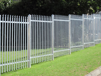 White steel palisade fence in ladder type, installed on the grass land, the posts are deeply buried in the ground.